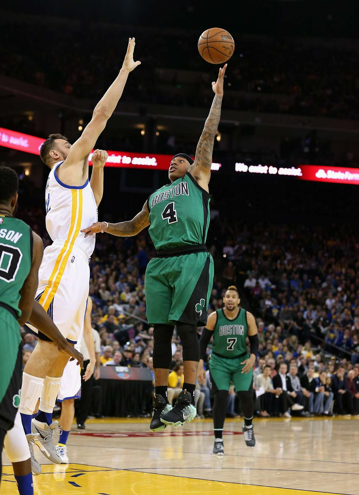 Isaiah Thomas #4 of the Boston Celtics shoots over Andrew Bogut at ORACLE Arena on April 1, 2016 in Oakland, California.