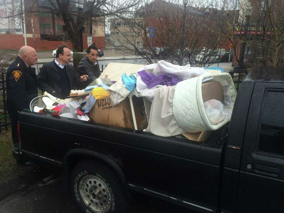 Police Chief Armando Perez, Mayor Joe Ganim and City Council Member Alfredo Castillo examine a pickup truck seized after Perez said he caught the occupants dumping the cargo illegally. Photo: Alex N. Gecan / Connecticut Post