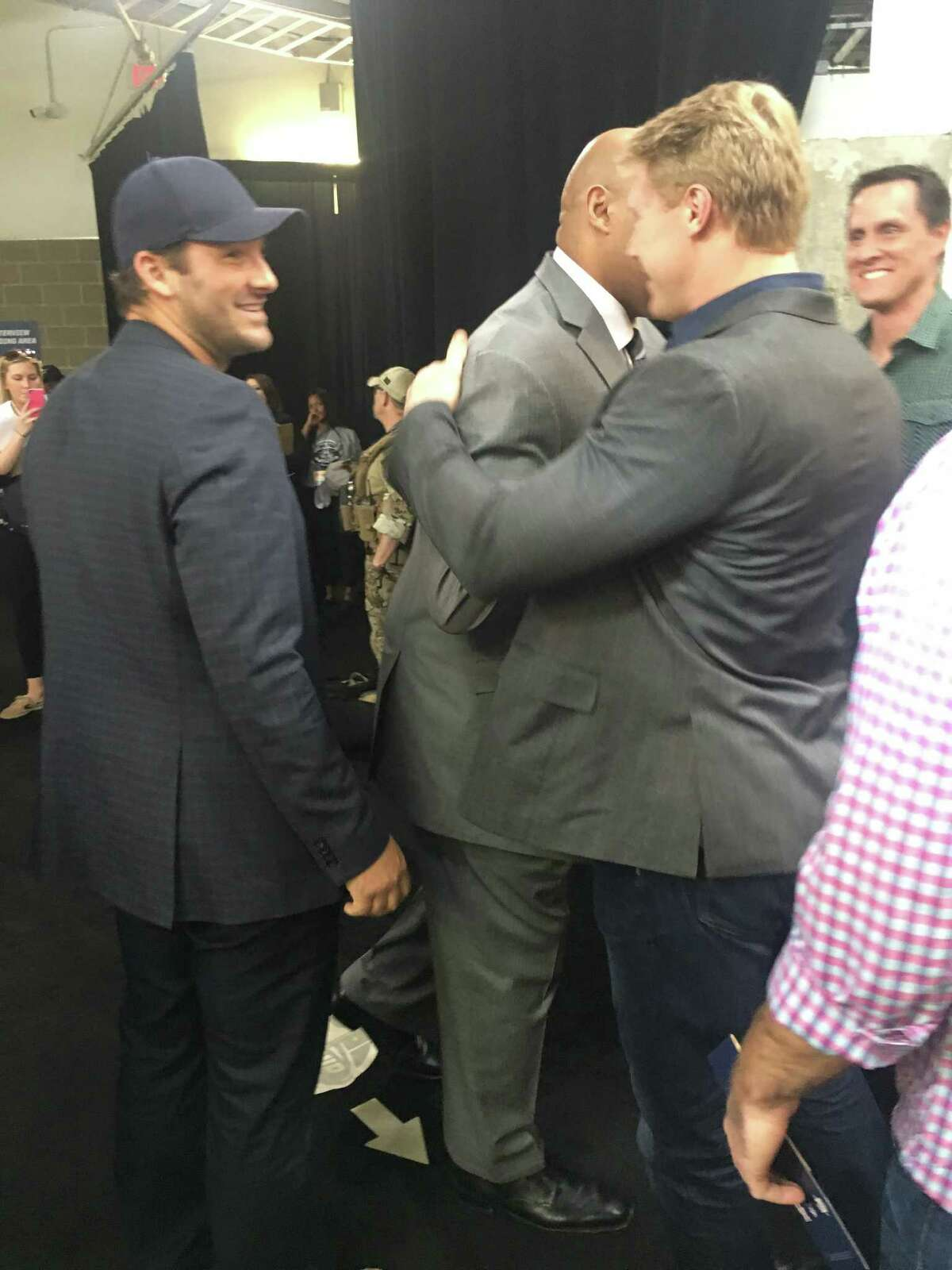 Tony Romo (left) makes his way into NRG Stadium for the Final Four as Barkley greets Romo's friends.