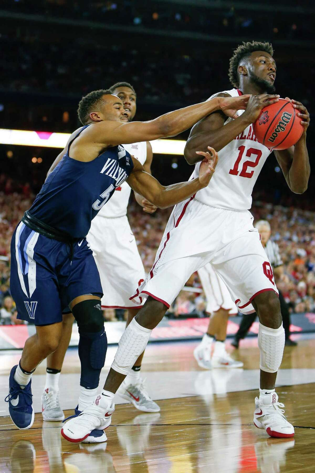 Oklahoma forward Khadeem Lattin (12) attempts to rip the ball away from Villanova guard Phil Booth (5) during the NCAA Final Four semifinals at NRG Stadium, Saturday, April 2, 2016, in Houston.
