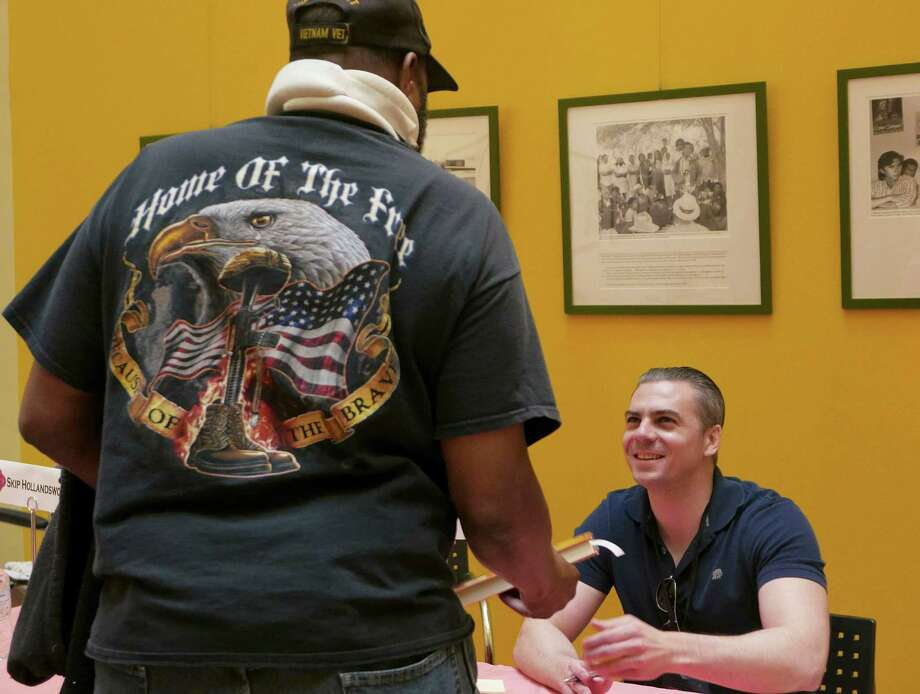 """Vietnam combat veteran Charles Ingram, left, has a book signed by author Brandon Caro, who was a Navy corpsman in Afghanistan in 2006 and 2007, at the San Antonio Book Festival on Saturday, April 2, 2016. Ingram said that he bought Caro's book, """"Old Silk Road,"""" for a friend who was a sniper in Iraq and Afghanistan and had traumatic experiences. """"I'm giving this to him as a healing balm for his soul,"""" Ingram said. """"After all, we are our brothers' keeper."""" About 100 authors read from their books and participated in panel discussions at the festival. There were also activities for children. Photo: Billy Calzada, Staff / San Antonio Express-News / San Antonio Express-News"""