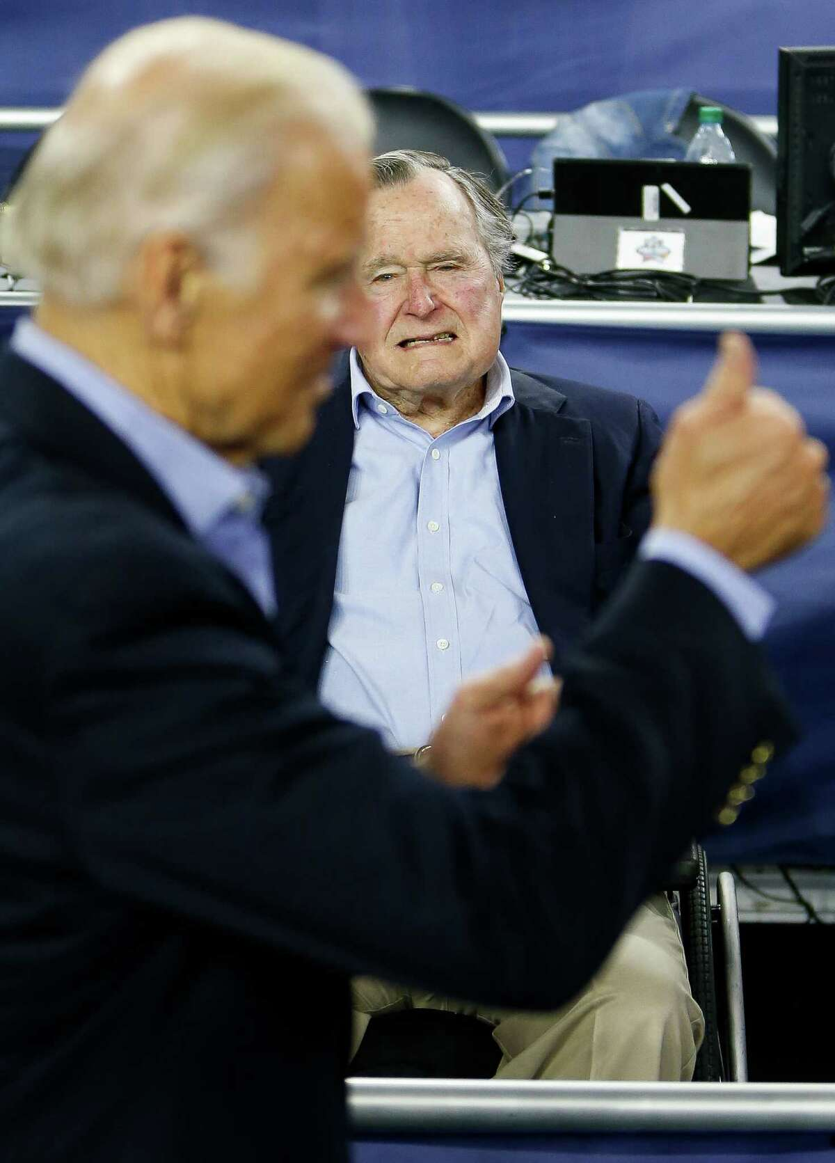 Vice President Joe Biden gives the thumbs up as former president George H.W. Bush watches the NCAA Final Four semifinals at NRG Stadium, Saturday, April 2, 2016, in Houston.
