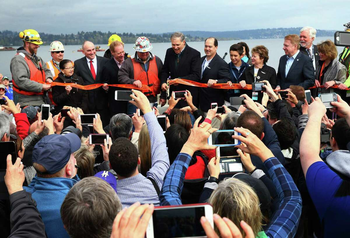 Washington Gov. Jay Inslee, center, cuts a ribbon officially opening the bridge.