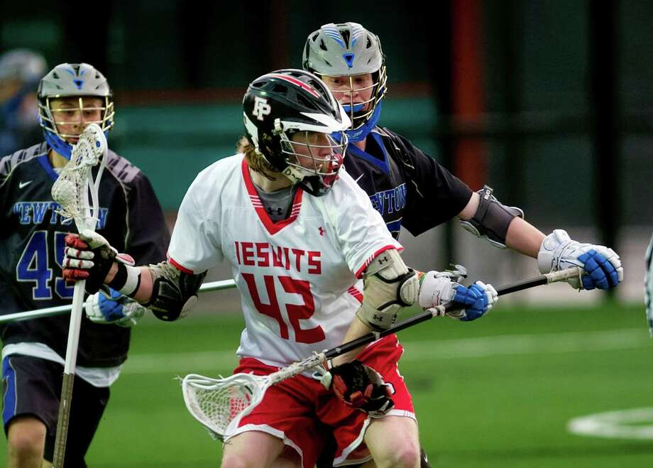 Fairfield Prep's Colin Smalkais tries to break past Newtown's Charlie Fletcher in Saturday's game. Smalkais had four goals in the Jesuits' 15-4 win. Photo: Christian Abraham / Hearst Connecticut Media / Connecticut Post