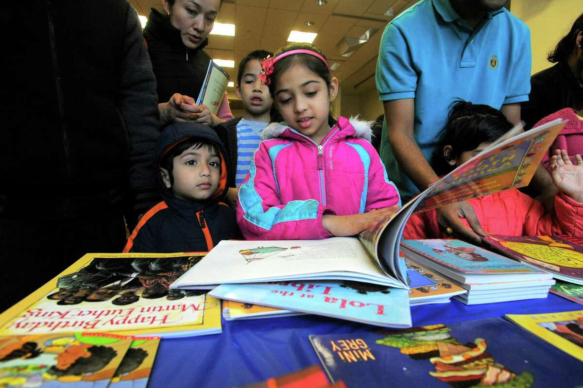 Krisha Parmar, 7 of Stamford, picks out one of three books each child would receive for participating in the Stamford Public Education Foundation bi-annual Reading is Fundamental Book Give-A-Way at the Ferguson Library in Stamford on April 2, 2016.