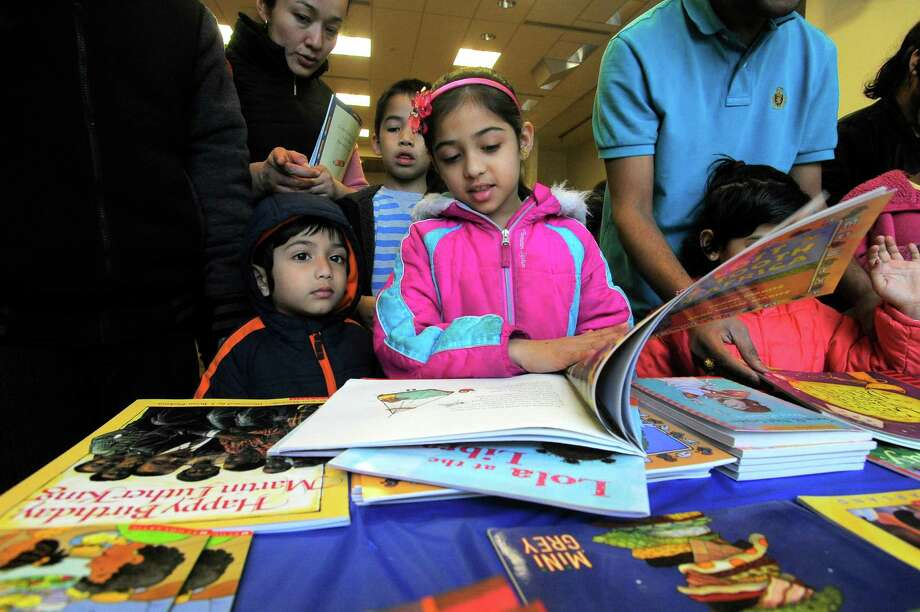 Krisha Parmar, 7 of Stamford, picks out one of three books each child would receive for participating in the Stamford Public Education Foundation bi-annual Reading is Fundamental Book Give-A-Way at the Ferguson Library in Stamford on April 2, 2016. Photo: Matthew Brown / Hearst Connecticut Media / Stamford Advocate