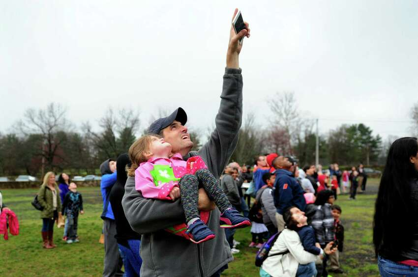 Lars Shurman and his daughter Sable, 3, watch rockets being launched during the 4th annual Space Day which was held at the Discovery Museum in Bridgeport, Conn., on Saturday Apr. 2, 2016. Just a few of the activities included a planetarium show, a lunar rock viewing, space science demonstrations and astronaut photos. A new feature for this year is Science on a Sphere. This show is a global display system which can show viewers any planet in the solar system, including Earth. Detailed topography, climate and other details are projected onto a six foot diameter hanging sphere.