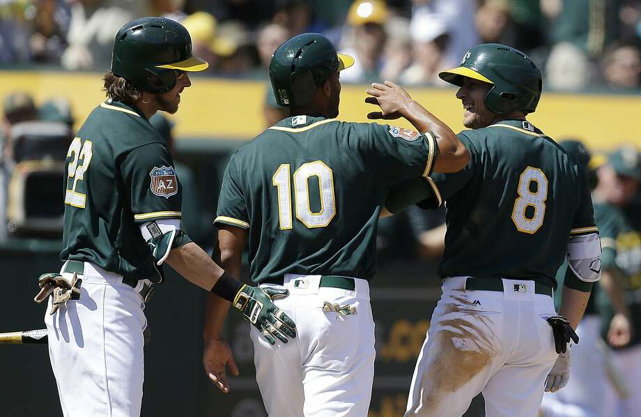 The A's Jed Lowrie (right) celebrates with Marcus Semien (10) and Josh Reddick after his inside-the-park home run in the third inning. Photo: Ben Margot, AP