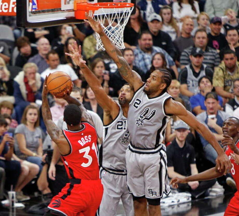San Antonio Spurs' Kawhi Leonard (2) and Tim Duncan (21) try and block a shot of Toronto Raptors' Terrance Ross (31) during the fourth quarter of an NBA basketball game, Saturday, April 2, 2016, in San Antonio. (AP Photo/Michael Thomas) Photo: Michael Thomas, Express-News / FR65778 AP