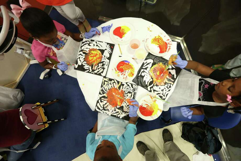 Patients paint after instructions by Professional Speed Painter Dan Dunn at Texas Children's Cancer and Hematology Center Wednesday, March 30, 2016, in Houston. Dunn had young patients use paints, but they had no idea that they were painting an image of a tiger until the last stroke of their brush.   The Periwinkle Foundation invited Dan Dunn to make a stop at Texas Children's Cancer and Hematology Centers to visit with children undergoing treatment. The children in the outpatient clinic spent the afternoon creating their own artwork and learning from master painter. Photo: Houston Chronicle / © 2016 Houston Chronicle