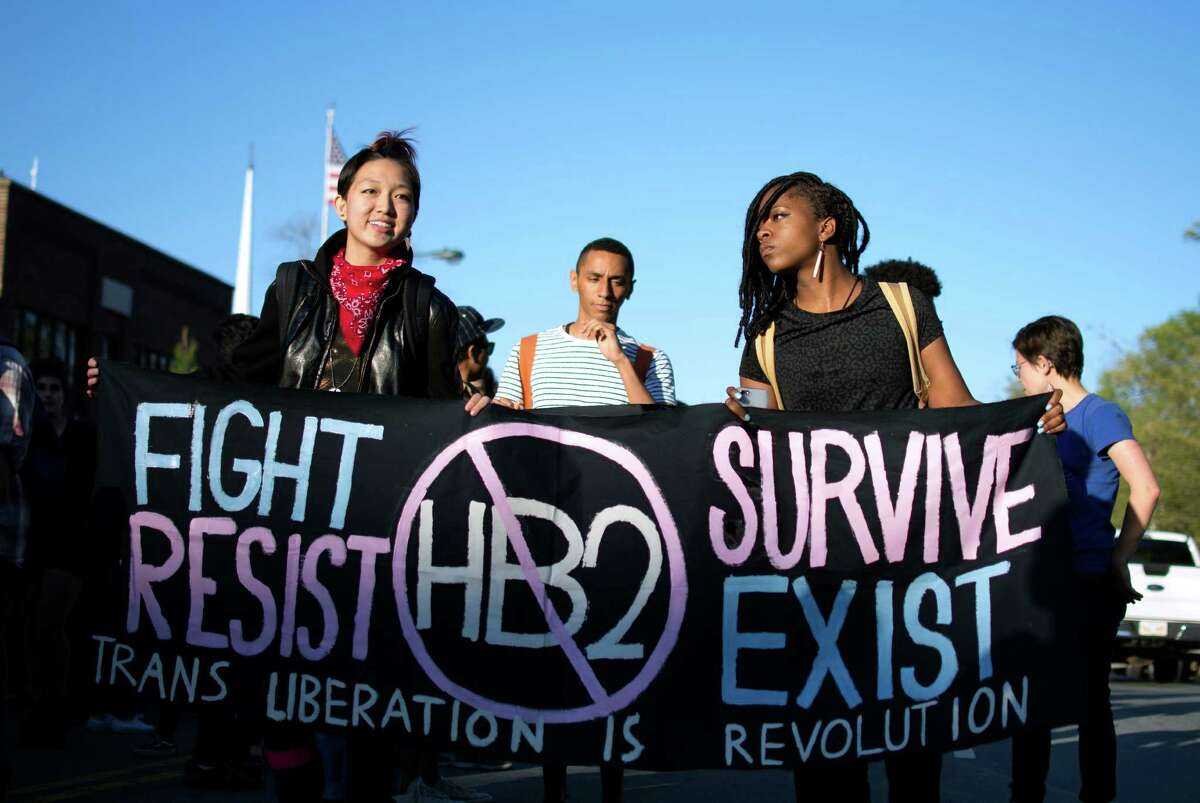 In this March 29, 2016 photo, Mitch Xia, left, rallies with other organizers during a march on Franklin Street against N.C. House Bill 2 in Chapel Hill, N.C. The new state law requires transgender people to use the restroom of their biological gender, not the gender with which they identify. Stung by setbacks related to their access to public restrooms, transgender Americans are taking steps to play a more prominent and vocal role in a nationwide campaign to curtail discrimination against them. (Whitney Keller/The Herald-Sun via AP) MANDATORY CREDIT