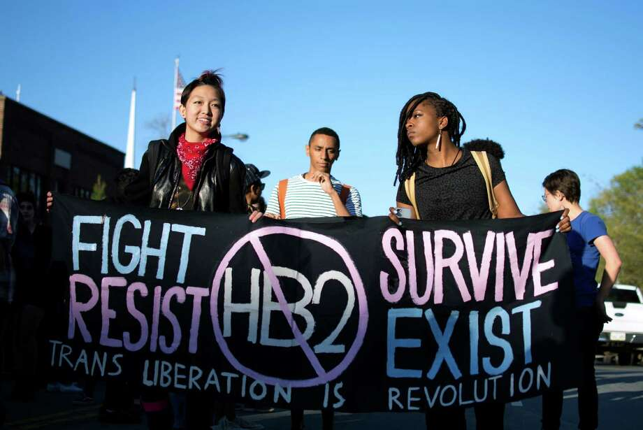 In this March 29, 2016 photo, Mitch Xia, left, rallies with other organizers during a march on Franklin Street against N.C. House Bill 2 in Chapel Hill, N.C. The new state law requires transgender people to use the restroom of their biological gender, not the gender with which they identify. Stung by setbacks related to their access to public restrooms, transgender Americans are taking steps to play a more prominent and vocal role in a nationwide campaign to curtail discrimination against them. (Whitney Keller/The Herald-Sun via AP) MANDATORY CREDIT Photo: Whitney Keller, AP / The Herald-Sun