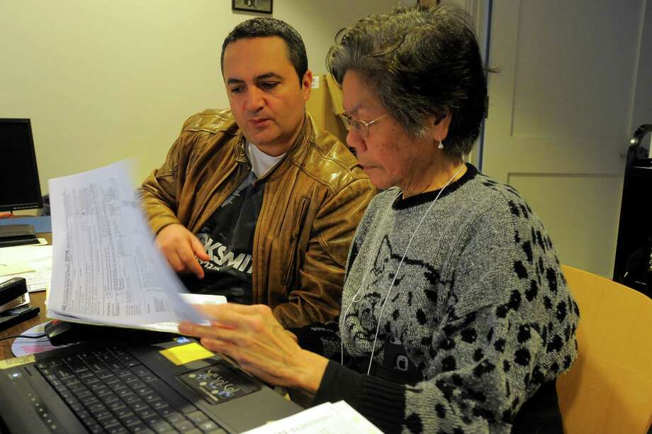 Iris Kishimoto of Norwalk, a volunteer with the AARP Foundation Tax-Aide program, assists Claudio Tudora of Stamford with filing his 2015 tax return on April 2, 2016 at the Weed Public Library in Stamford. Since 1968, the volunteer-based program  of the AARP Foundation Tax-Aide has been offering free tax preparation help to anyone who can't afford a tax preparation service, helping nearly 50 million low- to moderate-income taxpayers. Photo: Matthew Brown / Hearst Connecticut Media / Stamford Advocate
