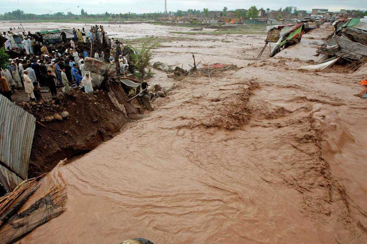 Pakistani villagers watch at flash flooding on the outskirts of Peshawar, Pakistan, Sunday, April 3, 2016. A Pakistani national disaster management official says flash floods triggered by torrential rains have killed dozens of people in the country's northwest.