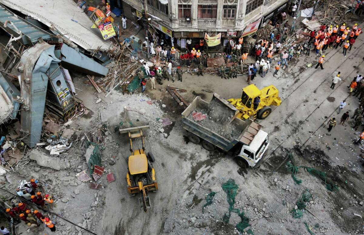 Excavator machines remove debris of a partially collapsed overpass in Kolkata, India, Friday, April 1, 2016. The overpass spanned nearly the width of the street and was designed to ease traffic through the densely crowded Bara Bazaar neighborhood in the capital of the east Indian state of West Bengal. About 100 meters (300 feet) of the overpass fell, while other sections remained standing.
