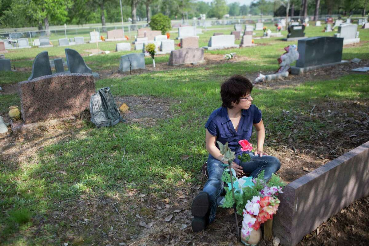"""Amy Beebe, 24, visits her brother's grave in Cleveland. Beebe's brother Joseph Beebe's death was ruled a homicide caused by """"battered child syndrome."""" When Amy Beebe was 11, she testified in court against her adoptive mother Edith Beebe and talked about the abuses she experienced along with her siblings that eventually took the life of her brother Joseph."""