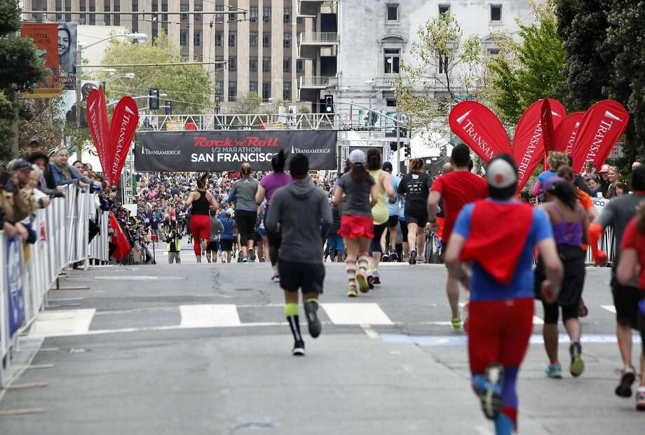Runners reach the finish line at Civic Center Plaza during last year's half marathon in San Francisco. The 2017 race closed major roads Sunday in the city as thousands of runners took to the streets. Photo: Brittany Murphy, The Chronicle