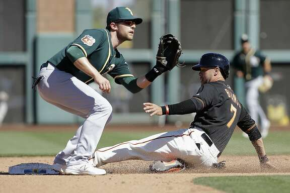 San Francisco Giants's Gregor Blanco, right, steals second base next to Oakland Athletics shortstop Jed Lowrie during the fourth inning of a spring training baseball game in Scottsdale, Ariz., Saturday, March 19, 2016. (AP Photo/Jeff Chiu)
