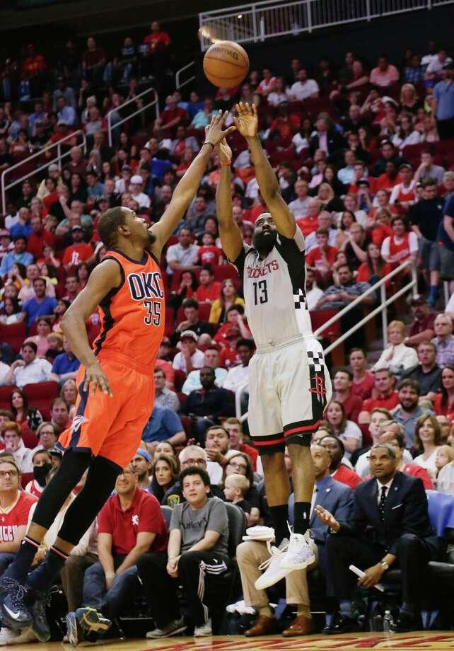 Houston Rockets' James Harden (13) shoots a three-point shot over Oklahoma City Thunder's Kevin Durant (35) during a basketball game Sunday, April 3, 2016, in Houston. Houston won 118-110. Photo: Bob Levey, AP / FR156786 AP