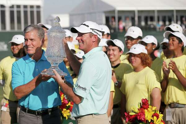 Shell Oil Co. President Marvin Odum hands Jim Herman the trophy after winning  the Shell Houston Open golf tournament at the Golf Club of Houston on , Sunday, April 3, 2016, in Humble, Texas.  Herman finished 15 under par.