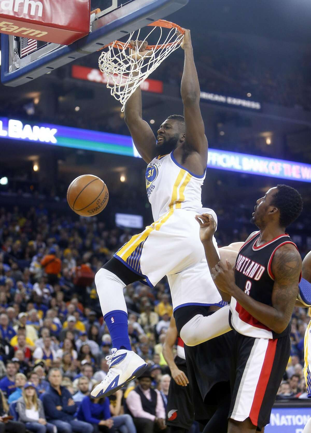 Golden State Warriors' Festus Ezeli dunks against Portland Trail Blazers' Al-Farouq Aminu in 1st quarter in NBA game at Oracle Arena in Oakland, Calif., on Sunday, April 3, 2016.