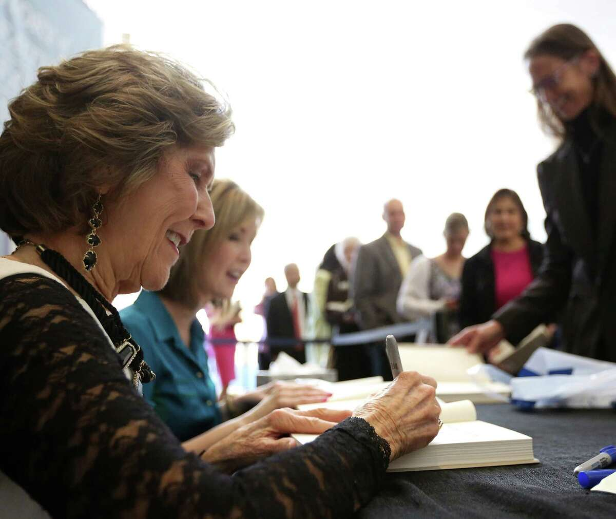 """Dodie Osteen signs a copy of her autobiography, """"If My Heart Could Talk,"""" which tells of the miracles she says have saved her and members of her family."""