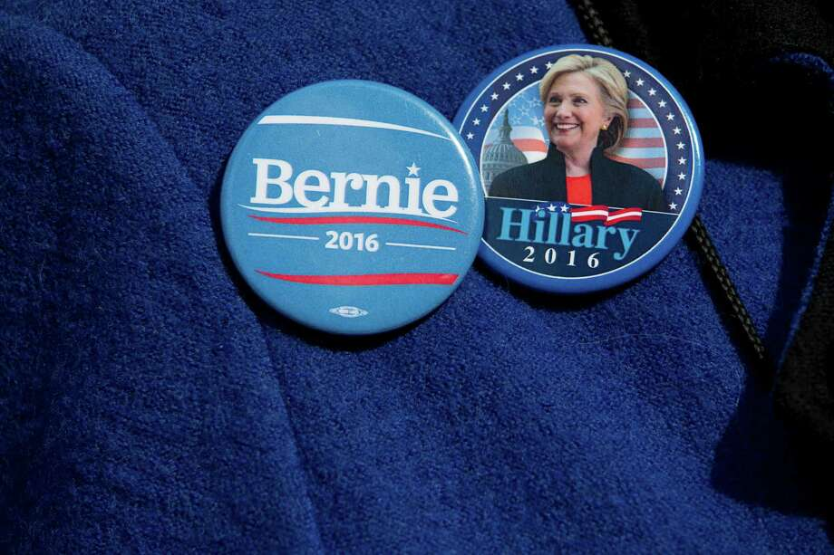 A demonstrator wears Democratic presidential candidate's Sen. Bernie Sanders, I-Vt., and Hillary Clinton buttons during a rally to condemn Republican presidential candidate Donald Trump's remarks about women and abortion, Thursday, March 31, 2016, in New York. (AP Photo/Mary Altaffer) ORG XMIT: NYMA103 Photo: Mary Altaffer / Copyright 2016 The Associated Press. All rights reserved. This m