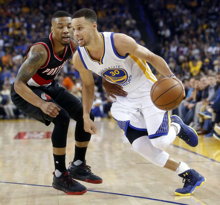 Golden State Warriors' Stephen Curry drives against Portland Trail Blazers' Damian Lillard in 2nd quarter in NBA game at Oracle Arena in Oakland, Calif., on Sunday, April 3, 2016. Photo: Scott Strazzante, The Chronicle