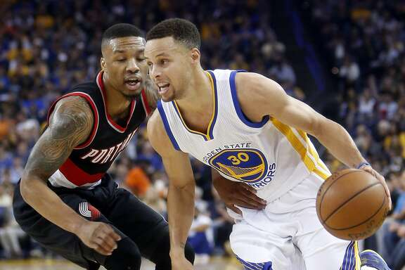 Golden State Warriors' Stephen Curry drives against Portland Trail Blazers' Damian Lillard in 2nd quarter in NBA game at Oracle Arena in Oakland, Calif., on Sunday, April 3, 2016.