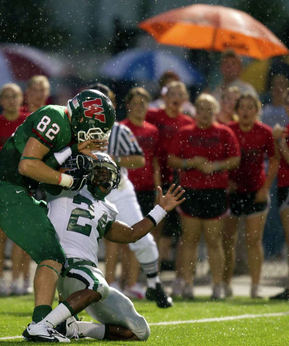 The Woodlands' Michael Cooper (82) wrestles the ball away from Hightower's Davin Simon (24) to score on a two-point conversion as rain falls on the first half in high school football action at Woodforest Stadium Friday, Sept. 3, 2010, in Shenandoah.