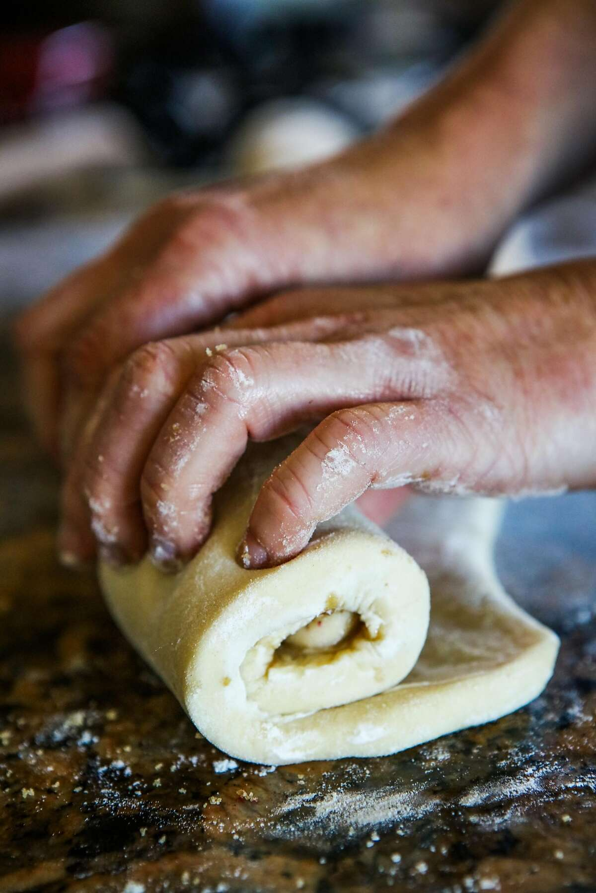 Pastry chef Brooke Mosley of Outerlands rolls the dough of strawberry-rhubarb sticky buns into a roll.