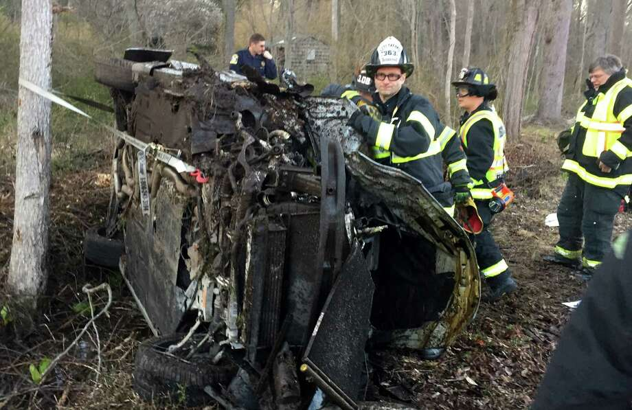 Firefighters work to extricate a driver trapped in a car that flipped on its side Sunday afternoon on the Merritt Parkway. Photo: Fairfield Fire Department / Fairfield Fire Department / Fairfield Citizen