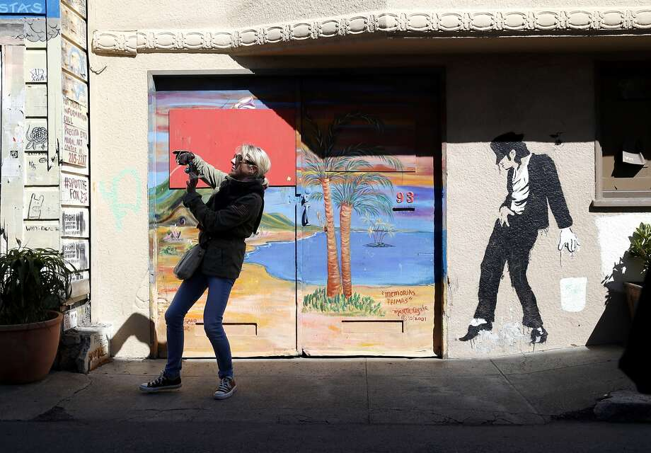 A woman, above, takes a photo of a mural during a recent Mission District tour for geographers. Photo: Connor Radnovich, The Chronicle