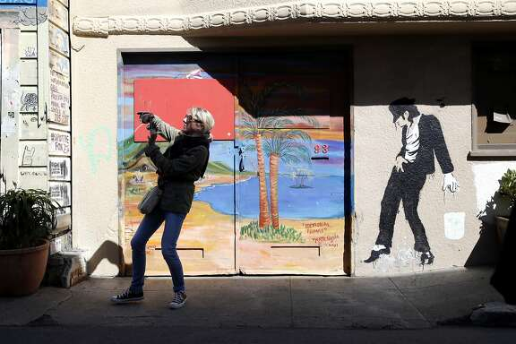 A woman takes a photograph of a mural with her phone during a tour of the Mission District for attendees of the Association of American Geographers annual conference in San Francisco, California, on Thursday, March 31, 2016.
