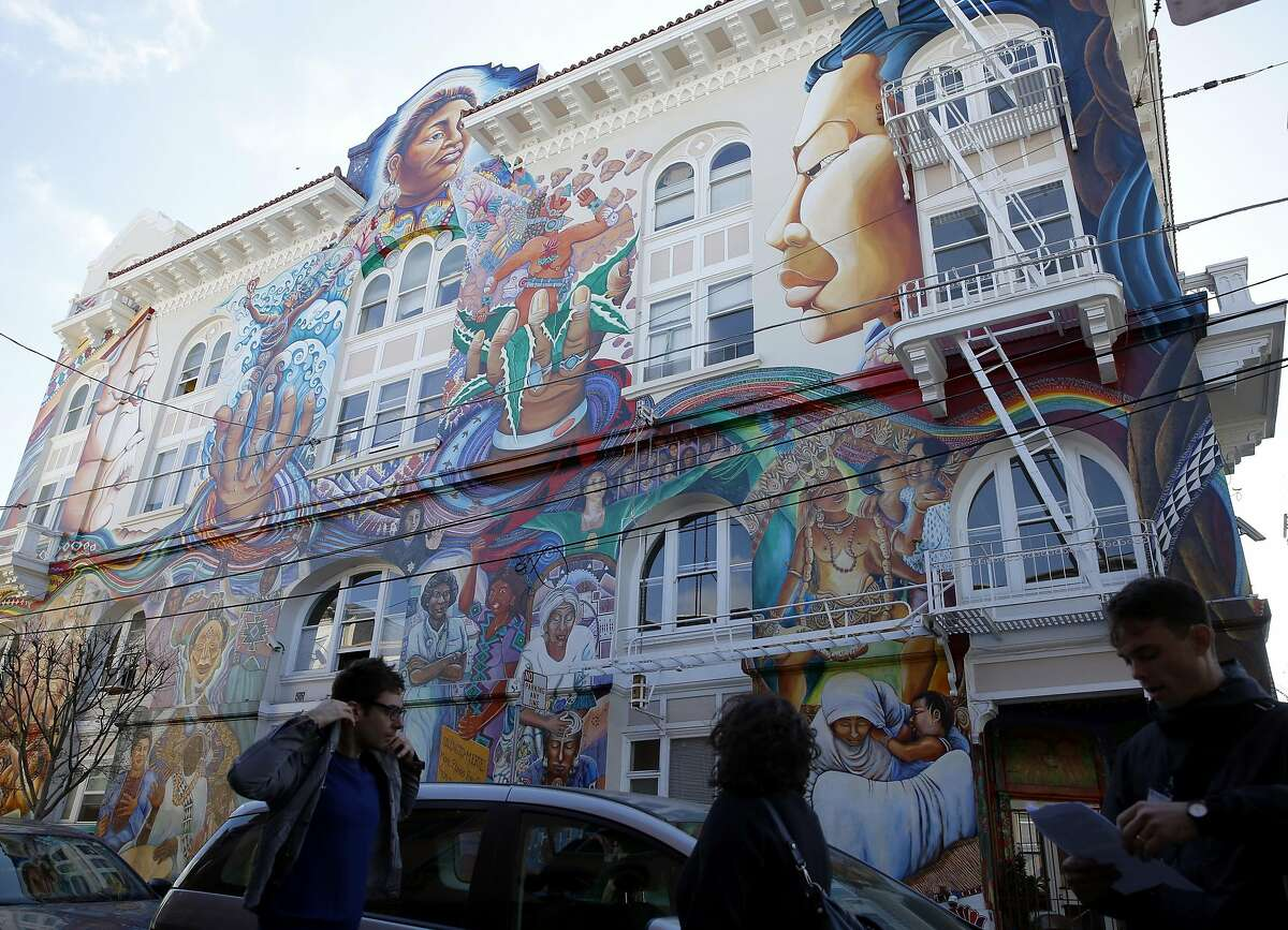 Members of a tour of the Mission District for attendees of the Association of American Geographers annual conference stand below a massive mural in San Francisco, California, on Thursday, March 31, 2016.