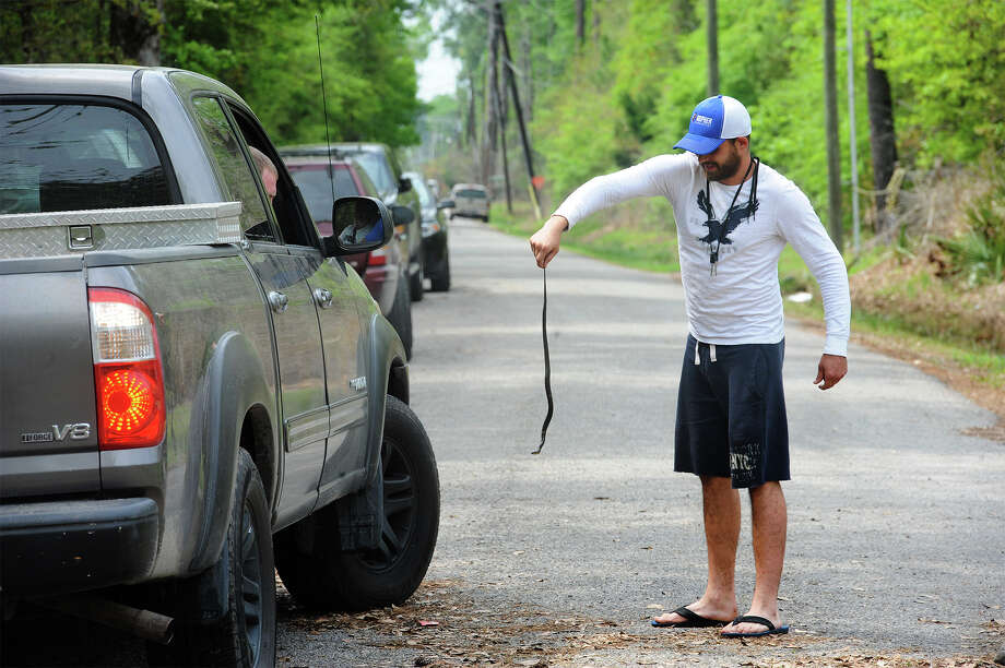 James Young shows off a snake to a passerby in Orange on Friday. Several snakes have been seen in the area since flood waters took over a section of the neighborhood. Photo taken Friday, March 18, 2016 Guiseppe Barranco/The Enterprise Photo: Guiseppe Barranco, Photo Editor