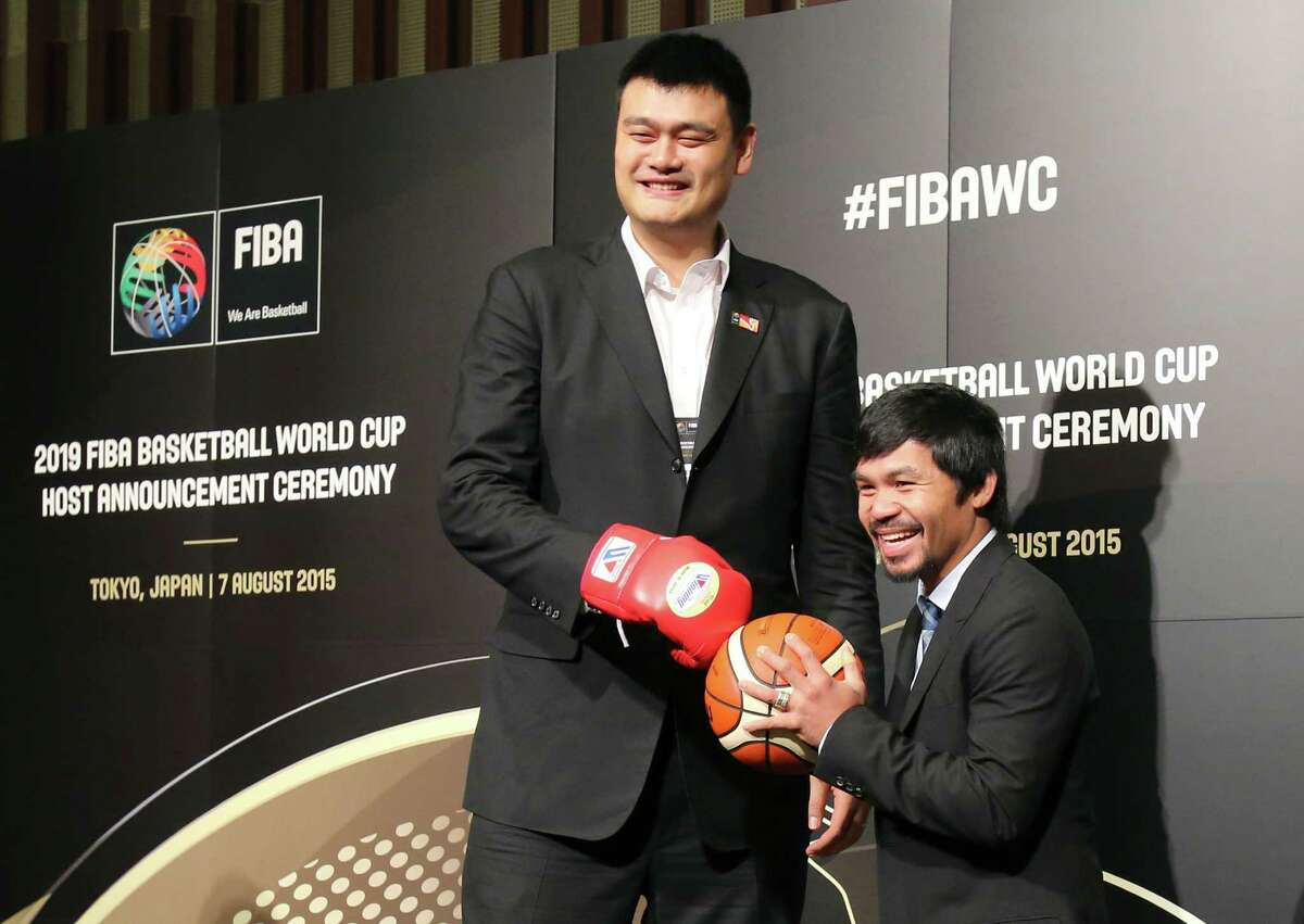 China 2019 Ambassador and former basketball star Yao Ming, left, and Philippine Congressman and eight-time world boxing champion Manny Pacquiao pose for a photo ahead of FIBA's announcement on whether the Philippines or China will host the 2019 Basketball World Cup, in Tokyo, Friday, Aug. 7, 2015.