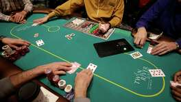 A game of poker is dealt to patrons at Twin River Casino, in Lincoln, R.I., on Feb. 3, 2016. Casinos far from Las Vegas are experimenting with different ways to draw millennials.