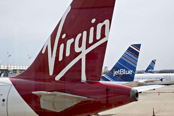 A Virgin America Inc. Airbus A319 airplane sits parked at a gate near JetBlue Airways Corp. airplanes at Ronald Reagan National airport (DCA) in Washington, D.C., U.S., on Monday, April 4, 2016. Alaska Air Group Inc. agreed to buy Virgin America for $2.6 billion, overcoming interest in the Richard Branson-backed carrier from JetBlue to secure a deal that bolsters its main West Coast business while opening up key airports in New York and Washington. Photographer: Andrew Harrer/Bloomberg