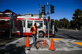 Tzanfow Saelee, a Bay Area Lightworks electrician replaces cables at the intersection of Diamond and Bosworth Streets, in San Francisco, California, on Monday, April 4, 2016. The construction project was initially completed last summer but is being modified because trucks and buses were having difficulty making proper turns without going up onto the curb.