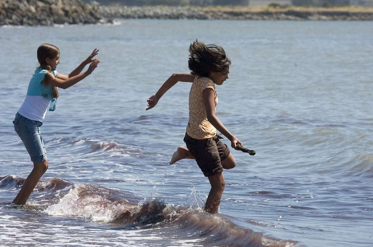 weather_0001_db.JPG Marlen Guzman, 11, and Olivia Orosco, 11, right, both of Winters, Ca., enjoy the surf along the shore of San Francisco Bay near Frontage Rd. which runs alongside Highway 80 in Berkeley, CA, on Thursday, June, 14, 2007. The children were celebrating a birthday party by visiting inland and escaping 102 degree heat in Winters, Ca. photo taken: 6/14/07 Darryl Bush / The Chronicle ** Marlen Guzman, Olivia Orosco (cq)
