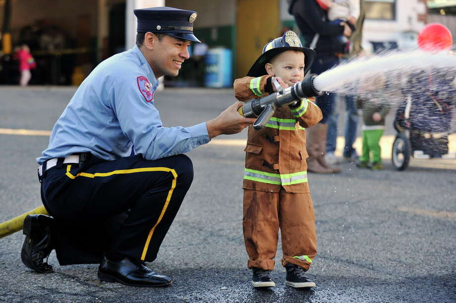 "Volunteer firefighter Nelson Franco shows his two-year-old son Aaron how to use a firehose during the annual Springdale Fire Company open house in the Springdale section of Stamford, Conn., on Sunday, Oct. 19, 2014. Nelson has been a volunteer with the Springdale Fire Company for three years. ""I've always waned to do it,"" Nelson says, "" It's fun to give back."" Photo: Jason Rearick / Jason Rearick / Stamford Advocate"