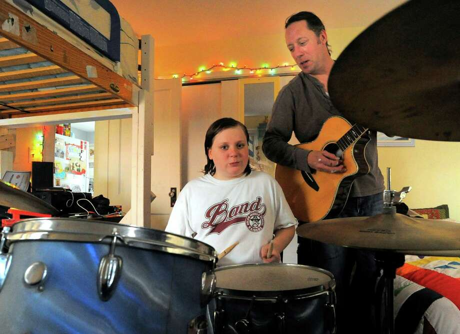 Charles Downs Gawlak plays drums while his father Charlie Gawlak strums his giutar at their Stamford home on April 1, 2016. Music loving families, like the Gawlaks, are sad the Alive@5 concert series is being limited to adults of drinking age. Charlie took his son to the last three concerts and hoped the experience would inspire his music. Photo: Matthew Brown / Hearst Connecticut Media / Stamford Advocate