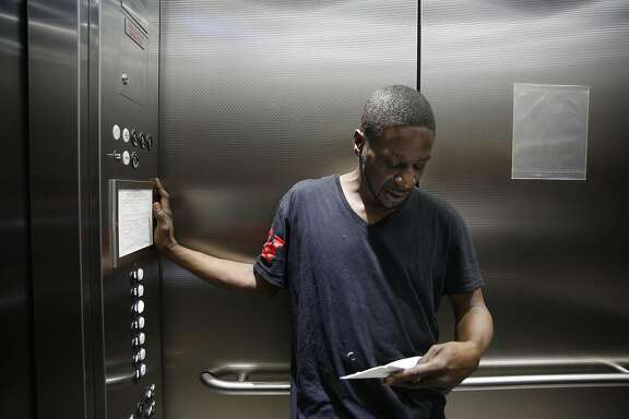 Vernon Mandigo, Franciscan Towers tenant who is formerly homeless, looks over mail in the elevator at the Franciscan Towers on Monday, April 4, 2016 in San Francisco, California.