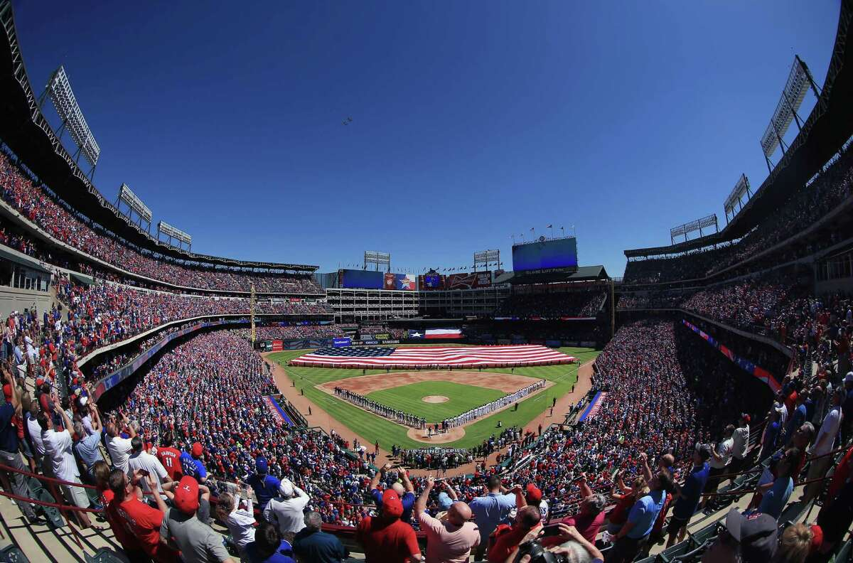 Fans look on as two fighter jets fly over during the National Anthem on Opening Day before the Texas Rangers take on the Seattle Mariners at Globe Life Park in Arlington on April 4, 2016 in Arlington, Texas.