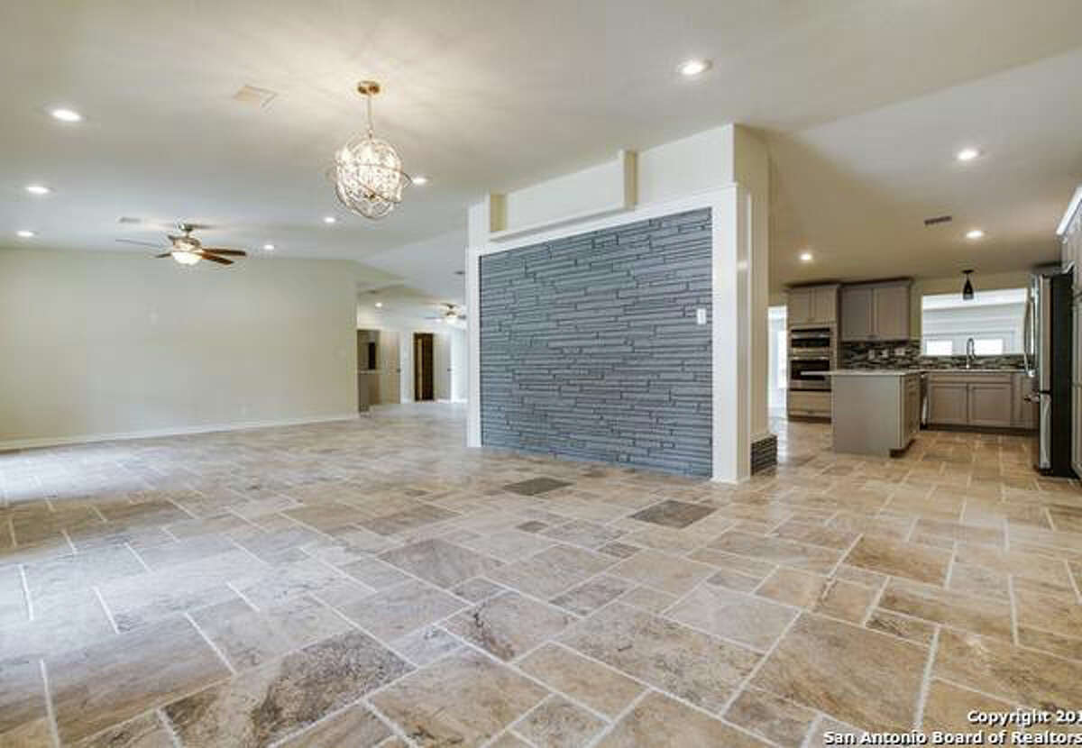 The home features a fireplace, soaring ceilings and tavertine tile.
