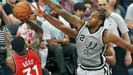 Kawhi Leonard gets over to block the shot of Terrence Ross as Tim Duncan also reaches on defense as the Spurs play Toronto at the AT&T Center on April 2, 2016.