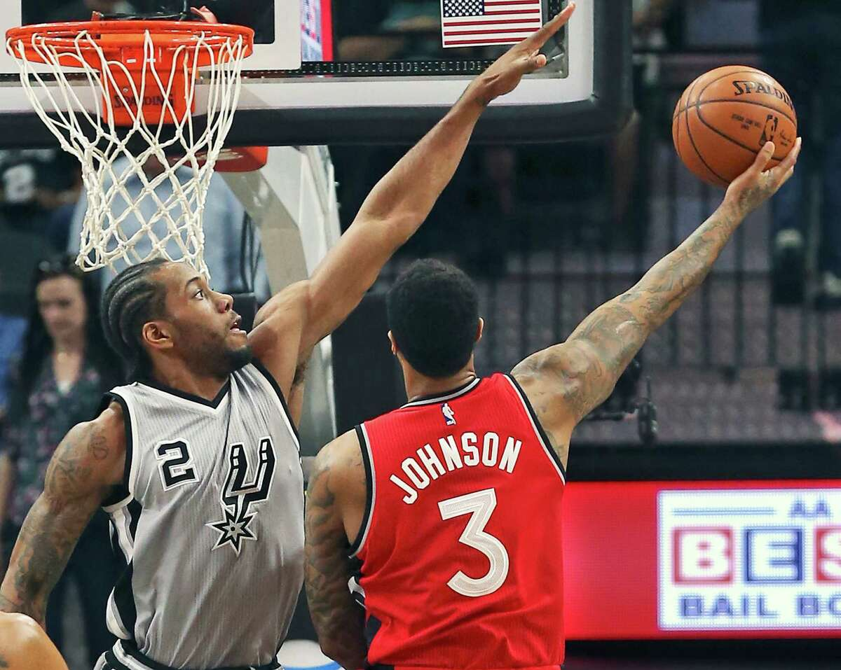 Kawhi Leoanard stretches out defending against James Johnson as the Spurs play Toronto at the AT&T Center on April 2, 2016.