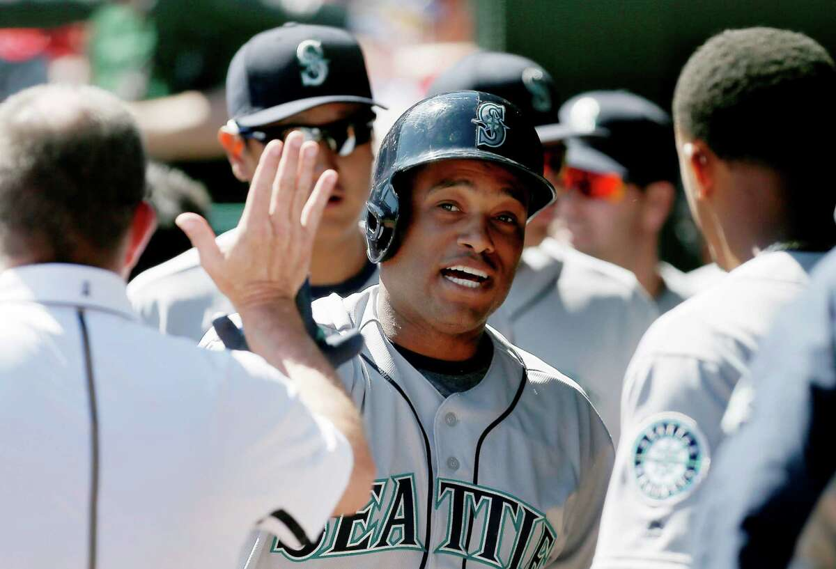 Seattle Mariners' Robinson Cano is congratulated by teammates after hitting a solo home run during the first inning of a baseball game against the Texas Rangers, Monday, April 4, 2016, in Arlington, Texas. (AP Photo/Brandon Wade)