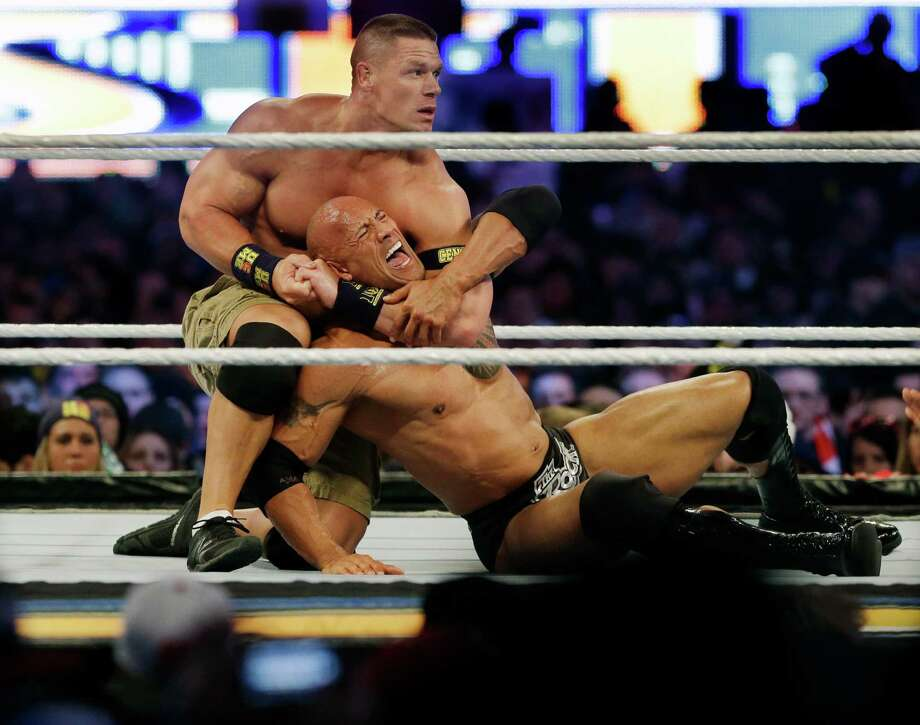 Wrestler John Cena, top, chokes The Rock as they face off during Wrestlemania in East Rutherford, N.J. Photo: Mel Evans, STF / AP